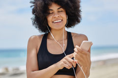 Afro american woman listening audiobook on mobile smiling. Portrait of afro american woman listening audiobook on mobile smiling Royalty Free Stock Photo