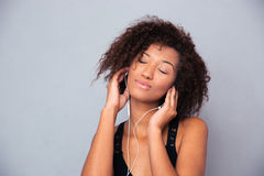 Afro american woman listening music in headphones Stock Images