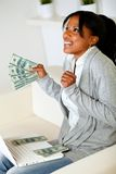 Afro-american woman looking up with dollars. Portrait of a excited afro-american woman looking up with dollars on one hand while is sitting in front a laptop at stock photo