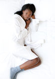 Afro-American woman lying on her bed Royalty Free Stock Photography