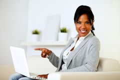 Afro-american woman pointing to laptop screen. Portrait of an afro-american woman pointing to laptop screen while looking to you Stock Photo