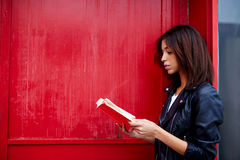 Afro american woman read literature while standing outdoors. Young female student reading interesting book while standing in the city on red wall background with Royalty Free Stock Images
