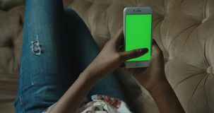 The afro-american woman is relaxing and chatting using the mobile phone with green screen while lying on the sofa. Close. Up view of the hands stock video