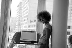 Afro american woman running on a treadmill Stock Photos