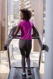 Afro american woman running on a treadmill Royalty Free Stock Images
