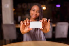 An Afro-American woman is showing a business card stock image