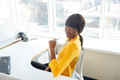 Afro american woman sitting at the table in office Royalty Free Stock Image