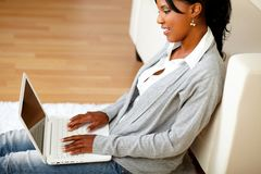 Afro-american woman using her laptop. Portrait of an afro-American young woman using her laptop while sits on the floor at home indoor Stock Photos