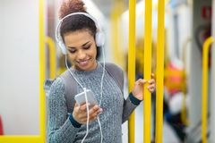 Young woman using mobile phone on subway Stock Photos