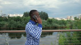 Black man calls on smartphone walking on waterfront in city park in slow motion. Afro american young guy is talking mobile phone, side view. Black man is stock footage