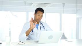 Afro-Amerikaanse arts die met geduldig, online videopraatje op laptop spreken stock foto's
