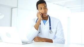 Afro-Amerikaanse arts die op telefoon in het ziekenhuis spreken royalty-vrije stock foto's