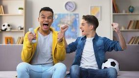Afro-Amerikaanse en Kaukasische vrienden die voor favoriet voetbalteam toejuichen, hobby stock video