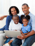 Afro-Amerikaanse familie die laptop op de bank met behulp van Stock Afbeelding