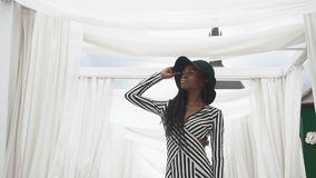 Afro-Amerikaanse jonge vrouw in het modieuze gestreepte cocktailkleding stellen op de achtergrond van haar luxeflats stock video