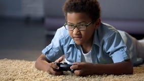 Afro-Amerikaanse jongen die absorbedly op nieuwe videospelletjeconsole spelen, huisactiviteit stock foto
