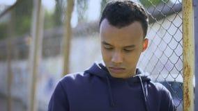 Afro-Amerikaanse jongen die op omheining, jonge vluchteling van dysfunctionele familie leunen stock videobeelden