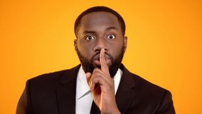 Afro-Amerikaanse mens die in kostuum stil teken, electionalstilte, nondisclosure maken royalty-vrije stock foto