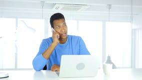 Afro-Amerikaanse mens die op telefoon, het aanwezig zijn vraag op het werk spreken royalty-vrije stock afbeeldingen