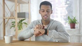 Afro-Amerikaanse mens die smartwatch voor het doorbladeren, e-mail en berichten gebruiken stock footage