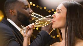 Afro-Amerikaanse mens en Aziatische dame het drinken champagne en het glimlachen, flirt bij partij stock videobeelden