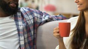 Afro-Amerikaanse mens en Kaukasische meisje het drinken thee en het babbelen zitting op bank stock footage