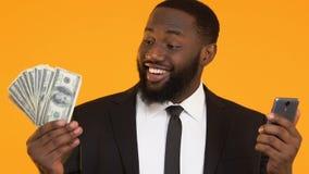 Afro-Amerikaanse smartphone van de managerholding en bos van dollars, online krediet stock footage