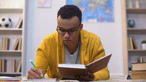 Afro-Amerikaanse student het schrijven poging, die voor belangrijke lezingen in universiteit voorbereidingen treffen stock videobeelden