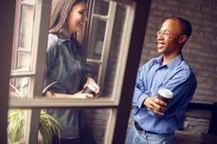 Afro-Amerikaanse supervisor die met jonge vrouw spreken stock afbeelding