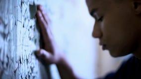Afro-Amerikaanse tiener wat betreft vlokkige muur, armoede en het levensmoeilijkheden, droefheid stock foto