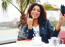 Afro Amerikaanse vrouw die pret hebben terwijl het fotograferen van met slimme telefoon in koffiewinkel Royalty-vrije Stock Afbeelding