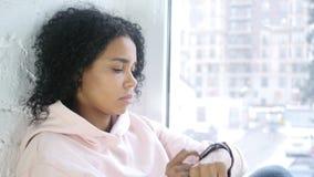Afro-Amerikaanse vrouw die smartwatch voor doorbladeren gebruiken, die bij venster zitten stock videobeelden