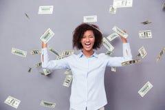 Afro Amerikaanse vrouw die zich onder regen met geld bevinden stock afbeeldingen