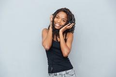 Afro Amerikaanse vrouw het luisteren muziek in hoofdtelefoons Royalty-vrije Stock Afbeelding