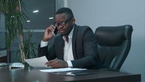 Afro-Amerikaanse zakenman die grafieken onderzoeken en op de telefoon spreken stock footage
