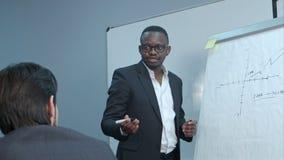 Afro-Amerikaanse zakenman die presentatie van een businessplan maken op flipchart Royalty-vrije Stock Afbeeldingen
