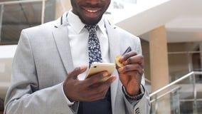 Afro-Amerikaanse Zakenman met bitcoin en mobiele telefoon in Modern Bureau stock footage