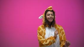 Afro--amerikan kvinna i rolig giraffpyjamasdans som isoleras på rosa bakgrund lager videofilmer