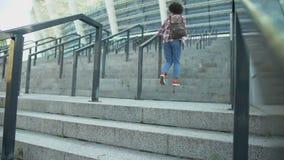 Afro--amerikan kvinnlig student som klättrar trappa som går till grupper på sportklubban arkivfilmer