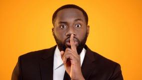 Afro--amerikan man i dr?kten som g?r det tysta tecknet, electionaltystnad, nondisclosure royaltyfri foto