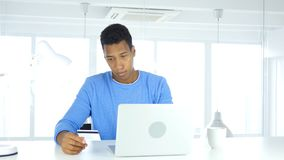 Afro--amerikan man som är upptagen i online-shopping, betalning vid kreditkorten Royaltyfri Foto