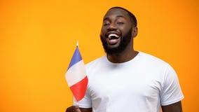 Afro--amerikan man som rymmer den franska flaggan p? ber?m f?r nationell ferie, n?rbild royaltyfri foto