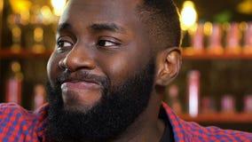 Afro--amerikan manrubbning om favorit- förlust för sportlag, hållande ögonen på match i bar stock video