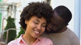 Afro--amerikan par som tycker om datumet, flicka som känner sig trygg i pojkvänarmar som ler lager videofilmer