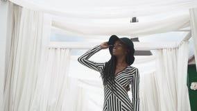 Afro--amerikanen gjorde randig den unga kvinnan i innegrej coctailklänningen som poserar på bakgrunden av hennes lyxiga lägenhete stock video
