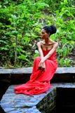 Afro-amerikanische Frau, die auf einem Hintergrund von Grünpflanzen sitzt lizenzfreies stockbild