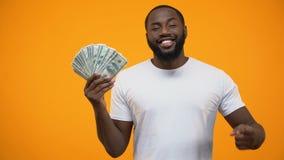 Afro-amerikanischer Mann, der Finger in Bündel Dollar, Investition zeigt stock footage