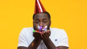 Afro-amerikanischer Mann in Schlagkonfettis des Parteihutes in Kamera, Geburtstagsspaß stock video