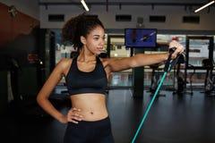 Afro- amerikansk kvinna som övar med konditionexpanderen på idrottshallen royaltyfria bilder