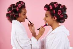 Afro- amerikansk liten flicka och mamma med hårrullar arkivfoton